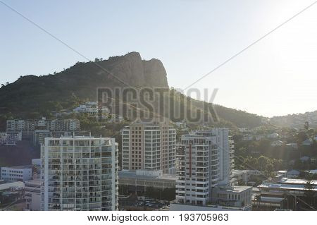 View of modern high-rise buildings in Townsville Queensland overlooked by a mountain peak backlit by a hot summer sun in a travel concept