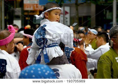 2017 05 28. SHINJUKU TOKYO JAPAN. A japanese boy sitting on his father shoulder at OMIKOSHI MASTURI FESTIVAL at HANAZONO JINJA. and carrying a portable shrine and walking around shinjuku city.