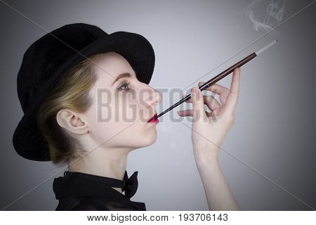 Young blond woman in a hat smokes through a mouthpiece