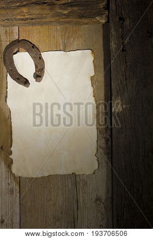 Rusty horseshoe and a sheet of paper on an antique door