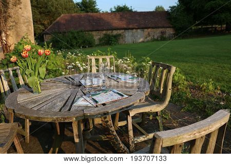 Outdoor wooden table in England set for two for dinner in the evening in the garden.