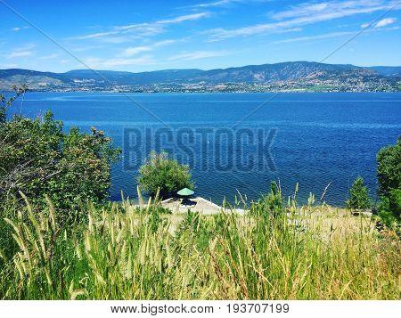 Tall Grass On Hilltop Overlooking Parasol On Lake Beach