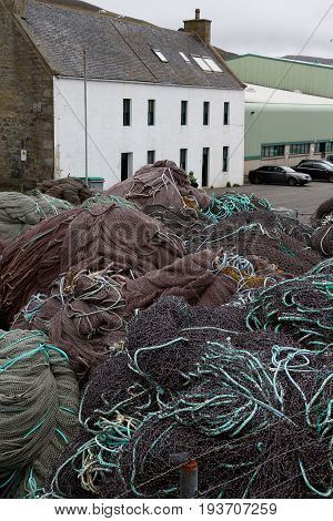 Piles of purple fishing nets with turquoise ropes on dock in front of white two-story house in Scalloway, Scotland harbor.