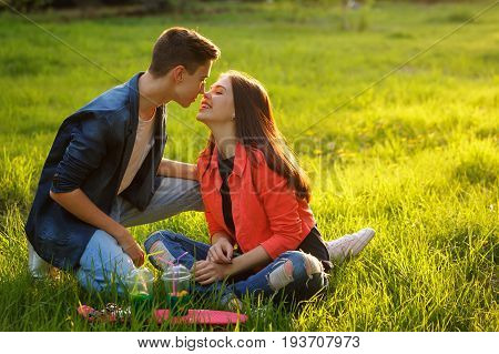 A loving couple of teenagers. Sudden picnic in the park at sunset. Teenagers are sitting on the lawn. They are kissing.