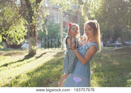 Family values. Mother and daughter. The mother holds the child in her arms. Same dresses and hairstyles. Family look