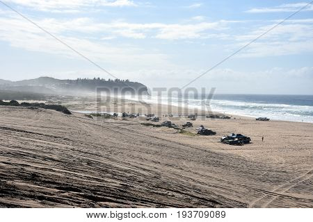 Horizontal landscape of the beach with cars. 4wd cars at Crokers creek (Belmont - Nine Miles - Beach NSW Australia). Redhead Point in the background.