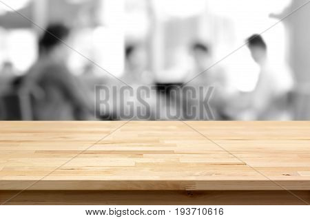 Wood table top on blurred monochrome background of people in cafe - can be used for montage or display your products