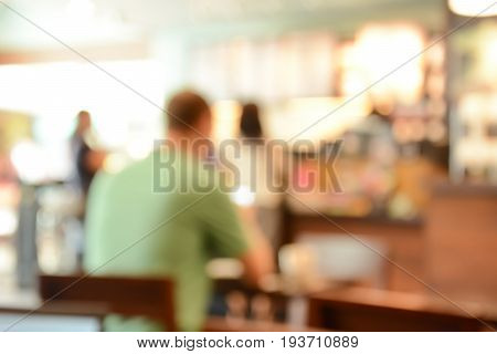 Blurred cafe interior with some people for background