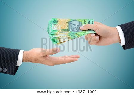 Businessman hands passing money Australian dollar (AUD) banknotes on gray background