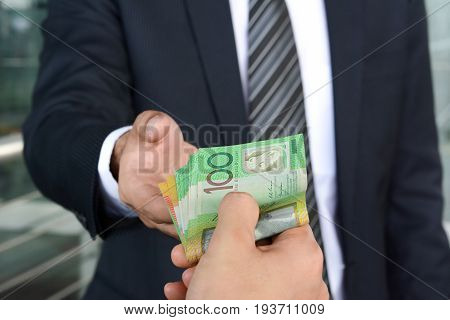 Businessman hands passing money Australian dollar (AUD) banknotes