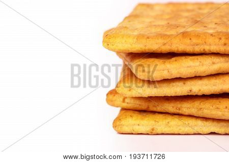 Close up rim of stacking healthy whole wheat cracker on white background with copy space