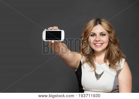 Studio shot of long haired smiling teenage girl showing smart phone with blank black touchscreen. All is on the gray background.