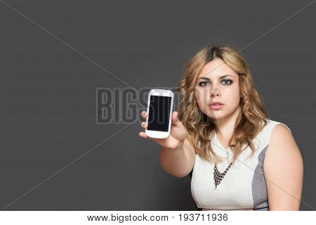 Studio shot of serious long haired teenage girl showing smart phone with blank black touchscreen. All is on the gray background.