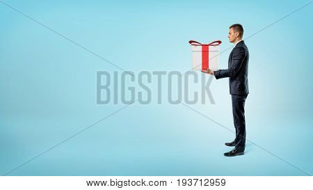 A businessman on blue background standing in side view and holding a gift box. Presents and gifts. Sales and promotions. Luck and fortune.