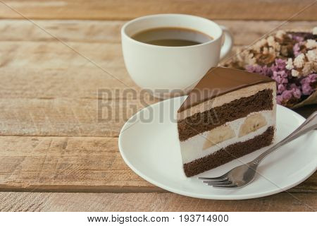 Banana chocolate cake on white plate served with black coffee. Chocolate cake layered with whipped cream and banana look so delicious. Enjoy eating at cafe restaurant with chocolate cake and coffee.
