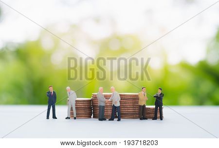 Stack of coins behind miniature businessman handshaking ,discussing and negotiating using as commitment ,agreement ,investment and partnership background concept.