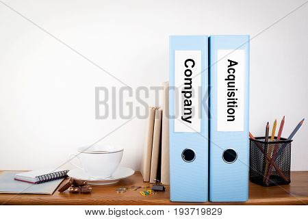 Company and Acquisition binders in the office. Stationery on a wooden shelf.