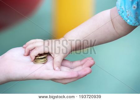 Child's small hand, takes a pile of small money from the palm of your hand