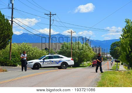 KALISPELL, MONTANA, USA - June 21, 2017: Fire and police officers walk in front of a police barricade near a grass fire