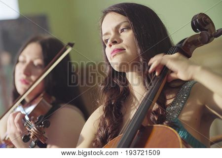Close up portrait of of two women playing a violoncello and alto
