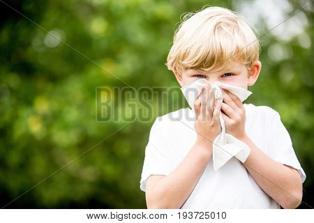 Child with allergy cleaning his nose with tissue in the nature
