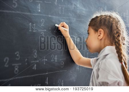 Tough day at school! Cute child near the blackboard indoors. Kid is learning in class. Complex math, arithmetic and examples. Numbers written with chalk on board.