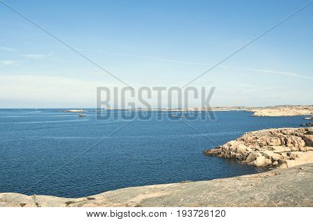 Beautiful summer season specific photograph. Large boulders and rocks together with rich blue/turquoise marine/ocean colors. Lovely lights and summer colors. Marine and ocean environment in summer.