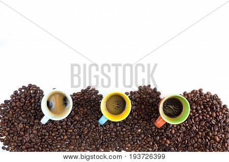 Colorful coffee cups lined up on coffee beans isolated on white background for web banner