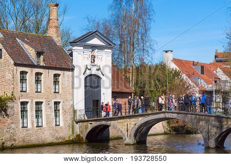 Bruges, Belgium - April 10, 2016: Canal and bridge view, St. Elisabeth Church entrance with tourists, in popular belgian destination