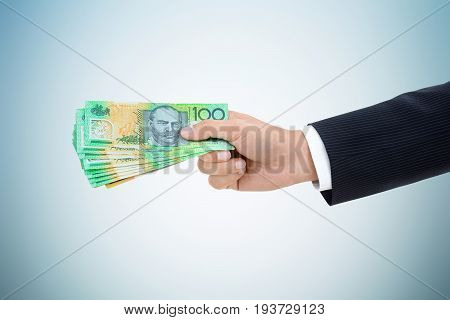 Businessman hand giving money Australian dollar (AUD) banknotes on white gray background