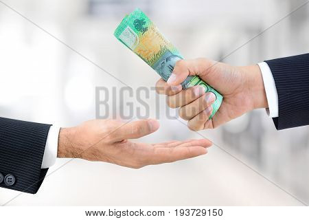 Businessman hands passing money Australian dollar (AUD) banknotes on white gray background