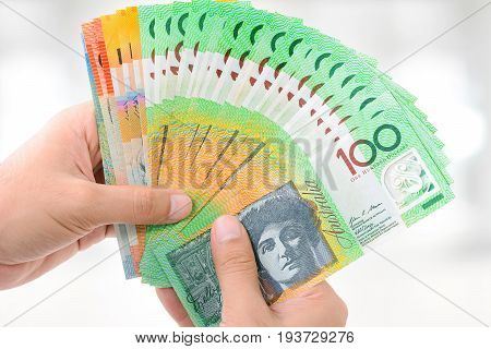 Hands holding money Australian dollar (AUD) banknotes on white gray background