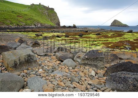 View of the ruins of Duntulm Castle and Tulm Island from the colorful beach of Duntulm Bay in the northern part of the Trotternish peninsula, Isle of Skye, Highlands, Scotland, UK