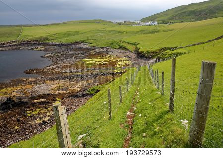 A coastal path leading to the colorful beach of Duntulm Bay in the northern part of the Trotternish peninsula, Isle of Skye, Highlands, Scotland, UK