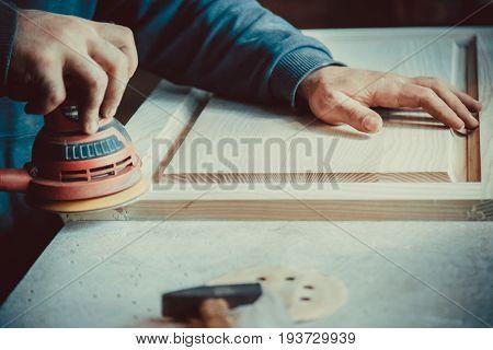 Close-up Of Carpenter Using Sander For Wood Furniture