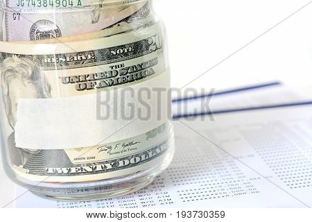 Money US dollar (USD) banknotes in the glass jar with blank label - financial business investment and accounting concepts