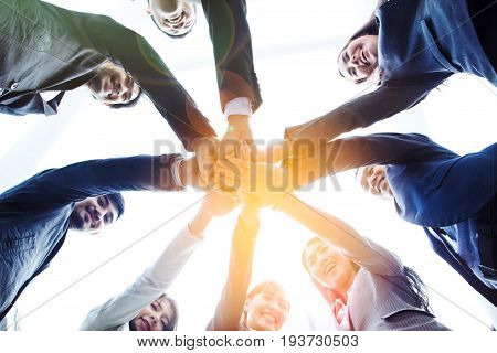 Business People bottom view of join hands put together looking down at camera Business team of happy smiling team building activity achieve success together successful business plan Corporate Meeting Teamwork Concept.