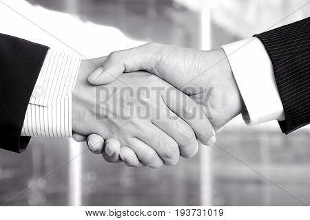 Handshake of businessmen in monochrome - congratulation greeting & business partner concepts