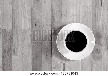 Coffee cup with black coffee on wood table top view with copy space monochrome effect