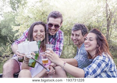 Happy Group Of Young Friends Toasting With Beer