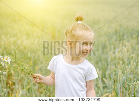 little girl with cunning smile, standing in field