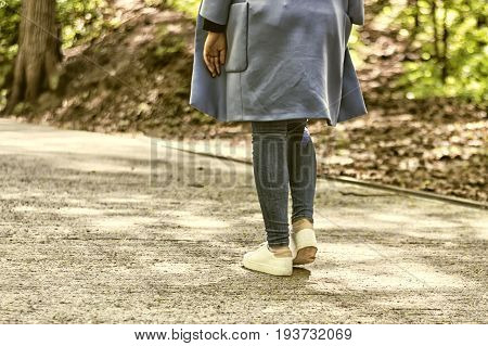 Girl walking away through alley with park at the sunny day. white sneakers and a blue coat a spring outing
