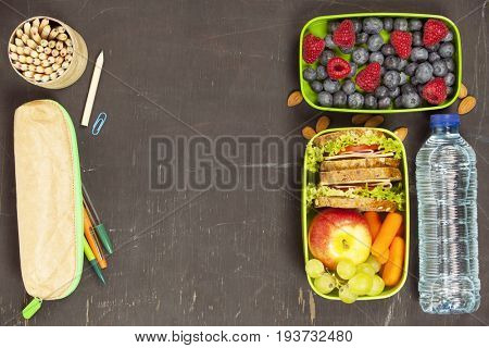Sandwich, apple, grape, carrot, berry in plastic lunch boxes, stationery and bottle of water on black chalkboard. Back to school concept.