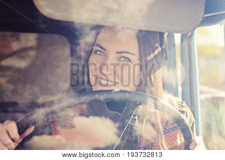 Woman Truck Driver In The Car. Girl Smiling At Camera And Holding The Steering Wheel.