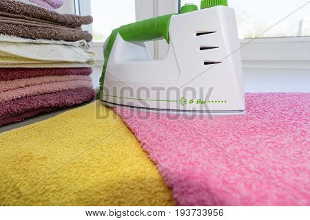 Ironing Linen With Iron. A Stack Of Ironed Towels Lying Next To The Iron. Hot Iron On An Ironing Boa