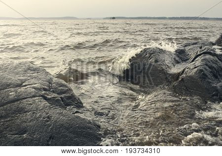 Beautiful summer season specific photograph. Large boulders and rocks together with stormy/rough sea and waves. Lovely lights and summer colors. Marine and ocean environment in summer.