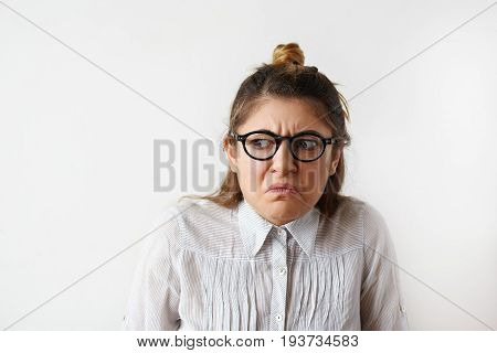 Studioshot of grumpy frowning young female with hair knot and nose-ring wearing glasses making wry face and looking away with unpleasant disgusted expression showing her negative emotions or disgust