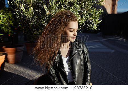 Outdoor shot of charming beautiful European student girl in black leather jacket having walk after lectures at college and enjoying warm sunshine on spring sunny day keeping her eyes closed