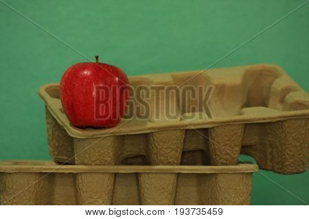 An apple on recycling paper tray with green background