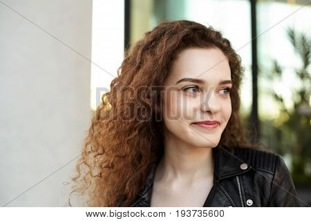 Oudoor urban portrait of cute beautiful young European female with curly hair and charming smile breathing fresh air during evening walk on city streets standing against modern building background